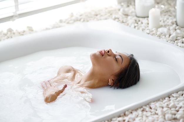 魅力的な女性がリラックスし、ミルク風呂でスキンケア。バスタブの女性、スパの美容とヘルスケア、バスルームのウェルネストリートメント、背景の小石とキャンドル