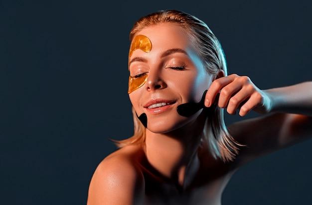 Привлекательная женщина удаляет цветные пятна с ее лица