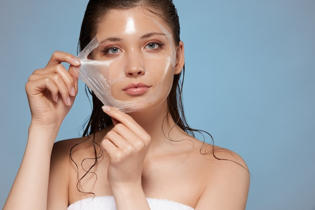 Attractive woman removing moisturizing mask and looking to the camera