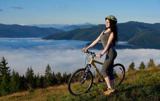 Привлекательная женщина всадника на велосипеде на желтый велосипед в горах, наслаждаясь восход солнца на летнее утро. туманные горы, леса на размытом фоне