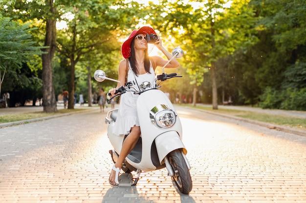 Donna attraente in sella a una moto in strada, stile di vacanza estiva, viaggiare, sorridere, felice, divertirsi, vestito elegante, avventure, scattare foto con la macchina fotografica d'epoca