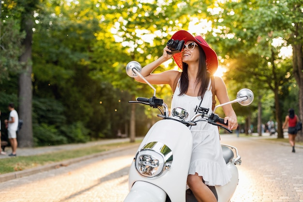 Attractive woman riding on motorbike in street, summer vacation style, traveling, smiling, happy, having fun, stylish outfit, adventures, taking pictures on vintage photo camera