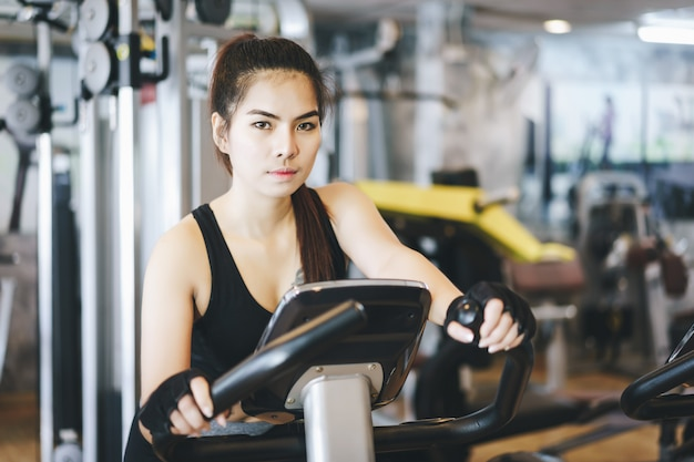 Attractive woman riding on the spinning bike.