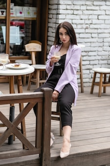 Attractive woman in romantic mood smiling in happiness sitting at table wearing pink jacket, stylish apparel, waiting for boyfriend on a date in cafe, drinking cappuccino, exited face expression