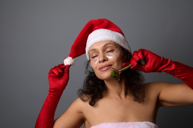 Attractive woman in santa costume uses jade roller massager for facelift and lymphatic drainage facial massage. skin care, cosmetology concept for christmas advertisement of beauty salons and spa