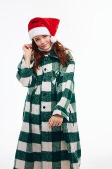 Привлекательная женщина санта шляпа клетчатое пальто улыбка изолированный фон