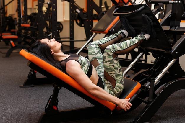 매력적인 여자는 체육관에서 훈련 세션에서 그녀의 다리를 흔들