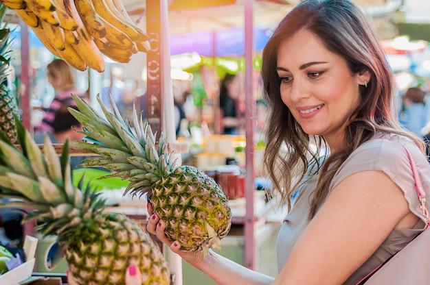 Привлекательная женщина покупки в зеленый рынок. макрофотография портрет красивая молодая женщина, собирание, выбор фруктов, ананасы. положительное выражение лица эмоция чувство здорового образа жизни
