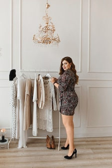 Attractive woman in short dress choosing outfit at home