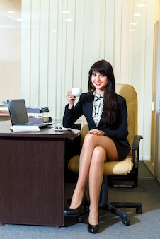 Attractive woman in a short skirt drinking coffee in the office