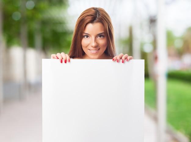 魅力的な女性は、白い空のプラカードを示しています