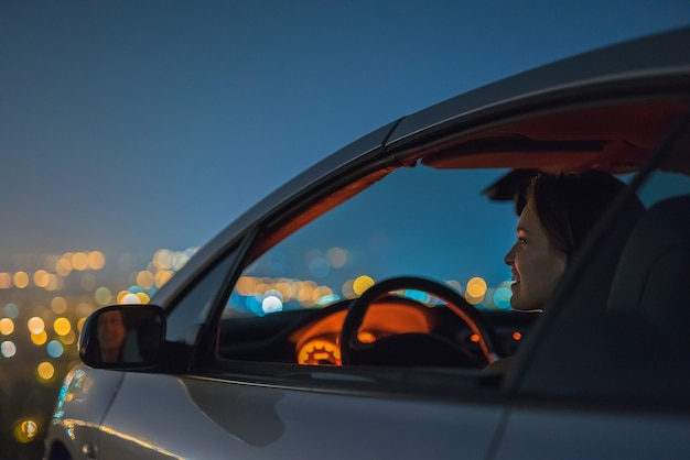 The attractive woman sit in the car on the background of the city. night time
