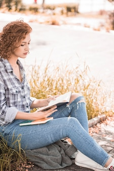 Attractive woman sitting on grass and reading book