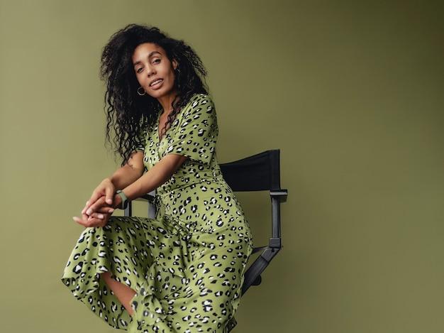 녹색 스튜디오 벽에 격리된 세련된 녹색 표범 무늬 드레스를 입고 의자에 앉아 있는 매력적인 여성
