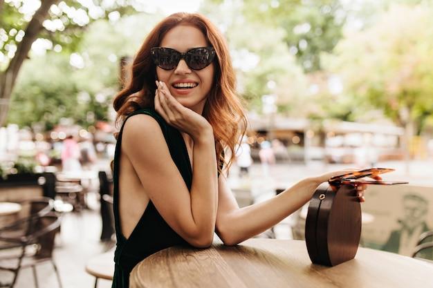 Привлекательная женщина, сидящая в городском кафе