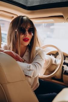 彼女の車に座っている魅力的な女性