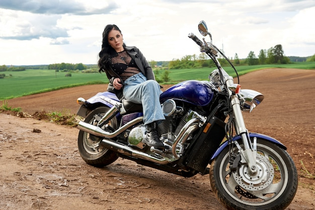 Attractive woman sitting on a motorcycle at sunset in a field.