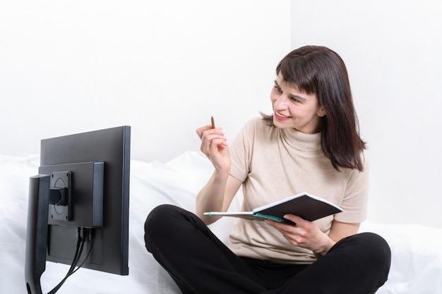 Привлекательная женщина сидит на диване с блокнотом и ручкой и пристально смотрит на монитор компьютера дома