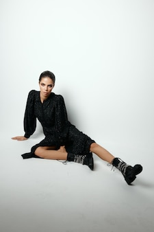 床に座っている魅力的な女性ファッショナブルな服ライフスタイル明るい背景