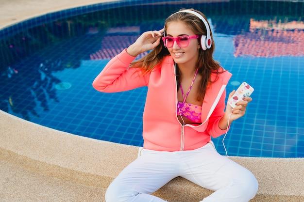 Donna attraente che si siede in piscina in felpa con cappuccio rosa colorato indossando occhiali da sole ascoltando musica in cuffia in vacanza estiva, stile sportivo