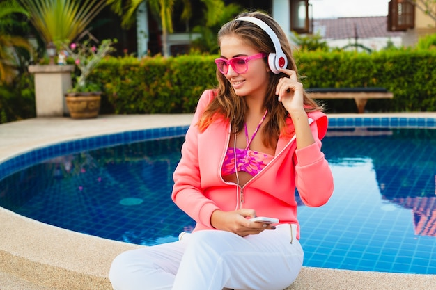 Attractive woman sitting at pool in colorful pink hoodie wearing sunglasses listening to music in headphones on summer vacation, sport style