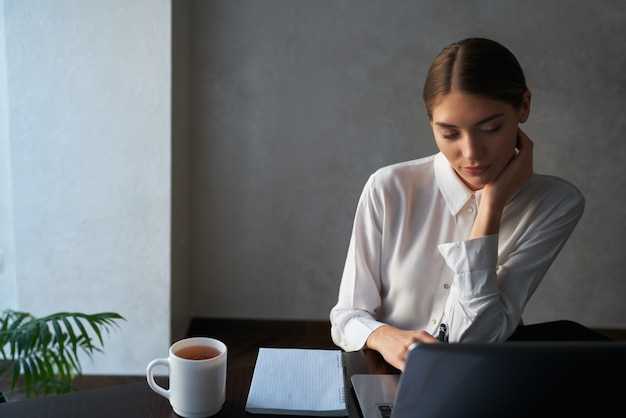Attractive woman sitting at table and working on laptop