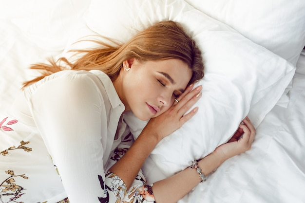 Attractive woman sleeping in bed in hotel room