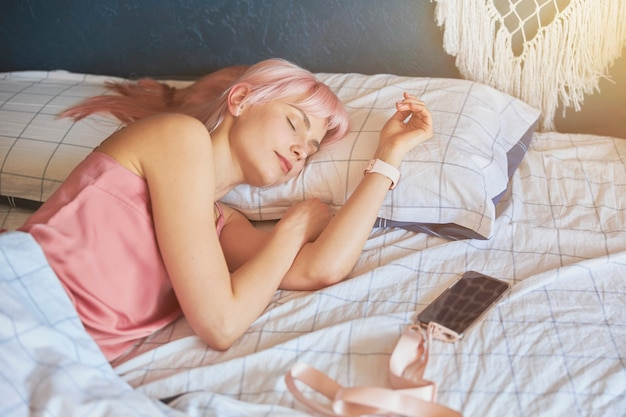 매력적인 여자는 크고 편안한 침대에서 빈 화면으로 전화 근처에서 잔다