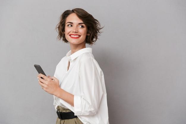 笑顔と携帯電話を保持している魅力的な女性、灰色の壁に隔離