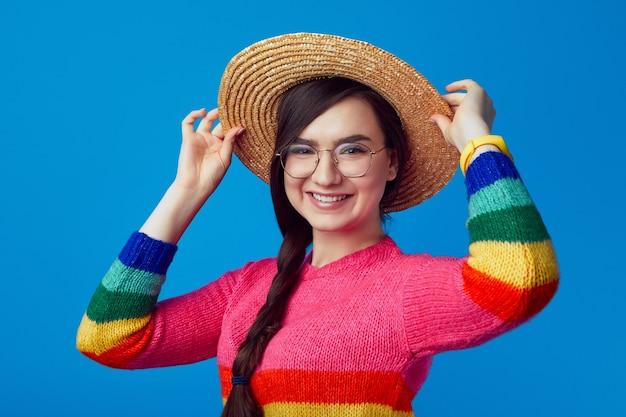 Привлекательная женщина улыбается и носить шляпу свитер радуги и очки