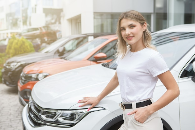 Attractive woman smiling, choosing new car at the dealership outdoor parking lot