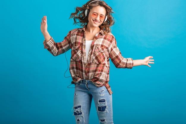 Attraente donna sorridente godendo l'ascolto di musica in cuffia in camicia a scacchi e jeans isolati su sfondo blu studio, indossando occhiali da sole rosa