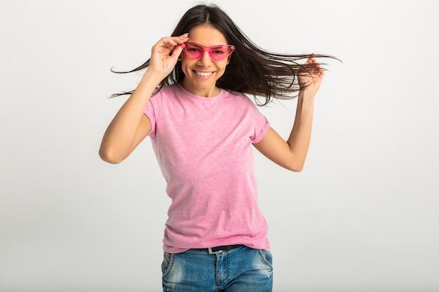 Attraente donna sorridente in maglietta rosa isolato indossando occhiali da sole rosa, lunghi capelli castani