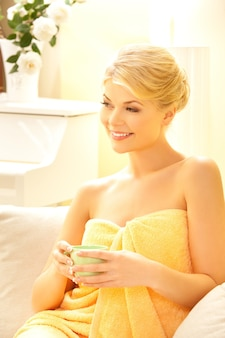 Attractive woman in spa salon with a cup