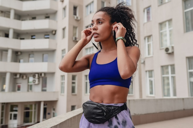 Attraente donna in abbigliamento sportivo fitness urbano sul tetto che fa allenamento