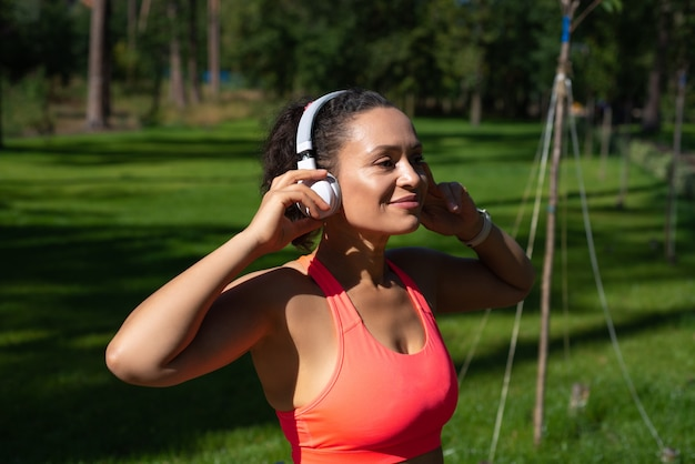 Attractive woman in sportswear standing in the park and touching headphones on her head