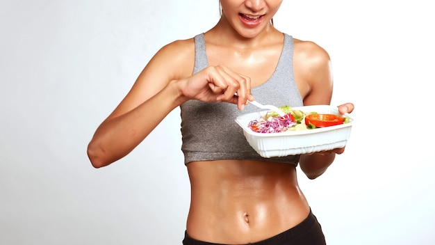 Attractive woman standing and eating salad.