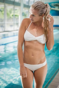 Attractive woman standing and looking away at the pool