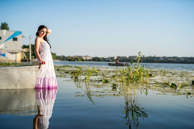 水中でボートの近くに立っている魅力的な女性