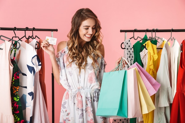 Attractive woman standing near wardrobe while holding colorful shopping bags and credit card isolated on pink