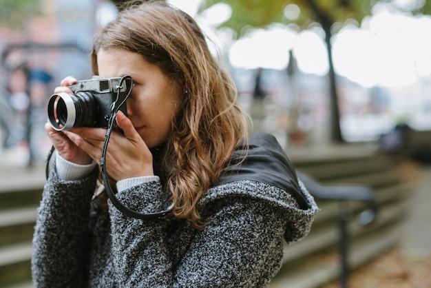 Attraente donna in piedi che indossa un cappotto grigio e scattare una foto con una fotocamera vintage