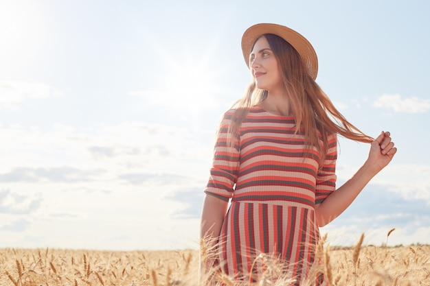 Attractive woman standing in wheat field, holding her hair with hands
