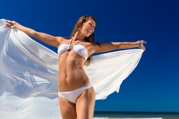 Attractive woman stands in the sun on beach