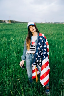 Attractive woman staying in field with American flag