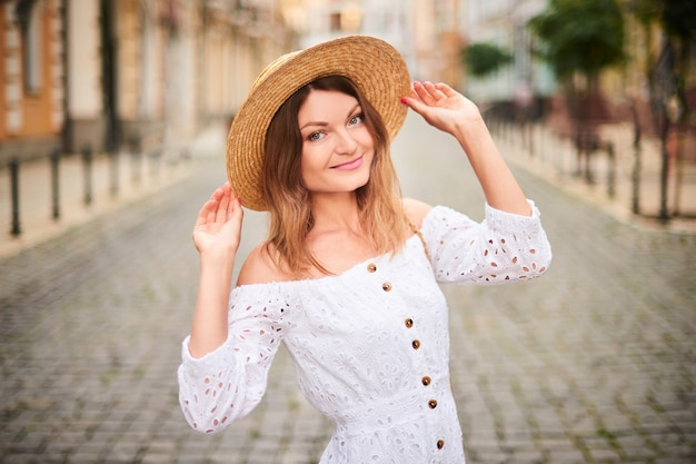 Attractive woman in straw hat and white sundress enjoying vacation