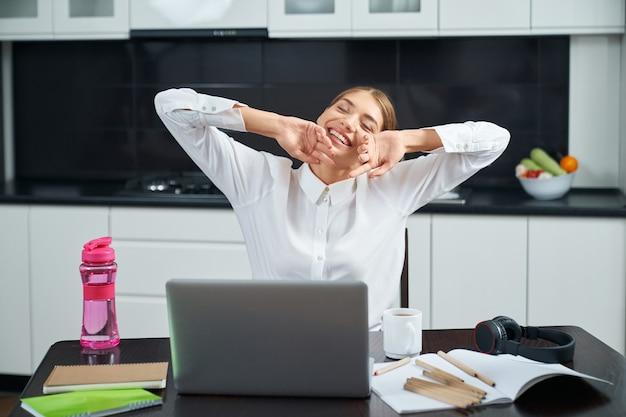 Привлекательная женщина, растягивая тело, сидя за кухонным столом во время удаленной работы на ноутбуке