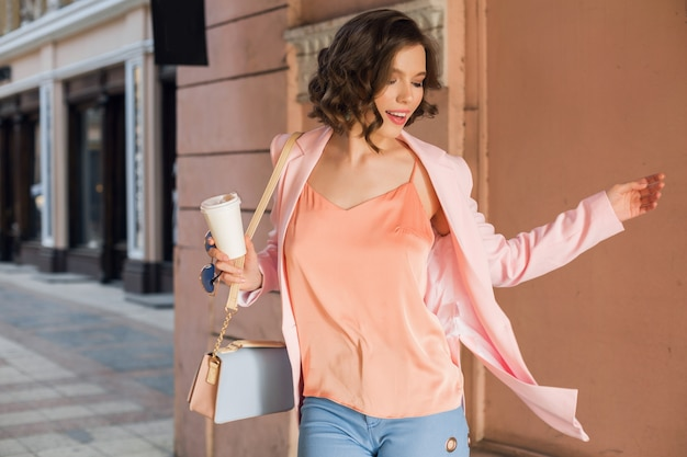 Donna attraente in abito elegante che cammina in città, moda di strada, tendenza primavera estate, umore sorridente felice, indossa giacca rosa e camicetta, gira intorno, è uscita, fashionista per lo shopping