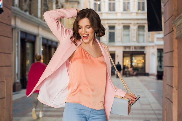 Attractive woman in stylish outfit walking in city, street fashion, spring summer trend, smiling happy mood, wearing pink jacket and blouse, spinning around, exited, fashionista on shopping