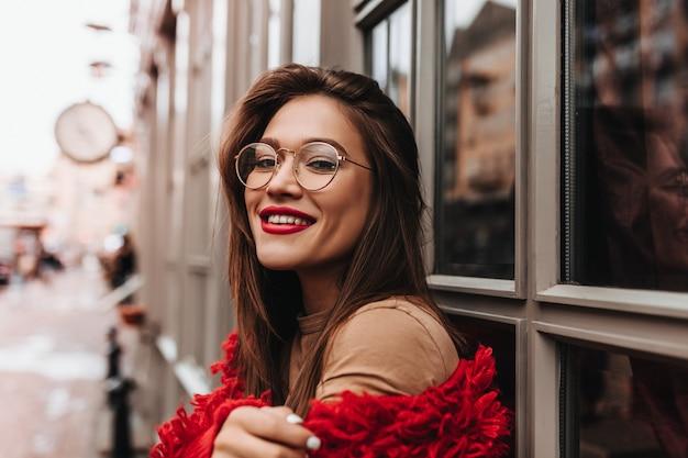 Donna attraente in vestito rosso alla moda in posa sulla strada. la donna dai capelli scuri con rossetto luminoso sorride.