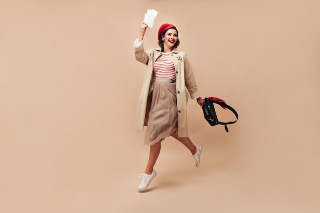 Attractive woman in stylish trench and red bright beret jumps on beige background and holds tickets on isolated backdrop.